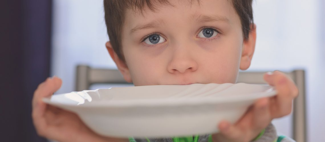 Hungry boy with beautiful eyes waiting for dinner. Holding empty plate in his hands